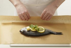 Wrapping whole sea bream in baking paper, with lemons, herb, and butter
