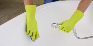 Hands cleaning bathtub