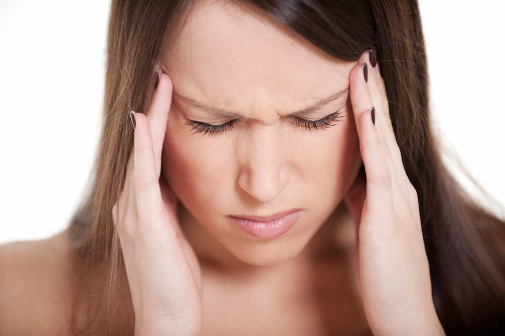 portrait of young woman with migraine against white background