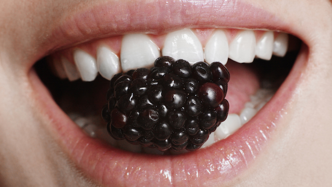 Young woman holding blackberry in teeth, close-up of mouth