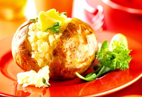 Plain jacket potato with butter on red plate