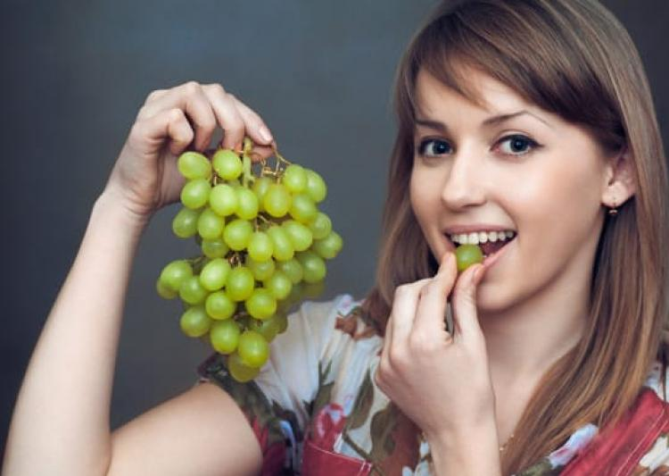 young-woman-eating-green-grapes-1486270425
