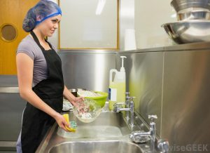 woman-in-black-apron-and-cap-washing-dishes