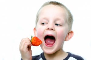 happy-little-boy-eats-strawberries